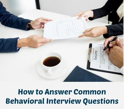 Hands passing resume across desk in behavioral interview situation