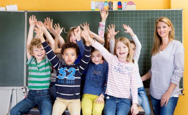 Preschool teacher and pupils with hands up in front of blackboard